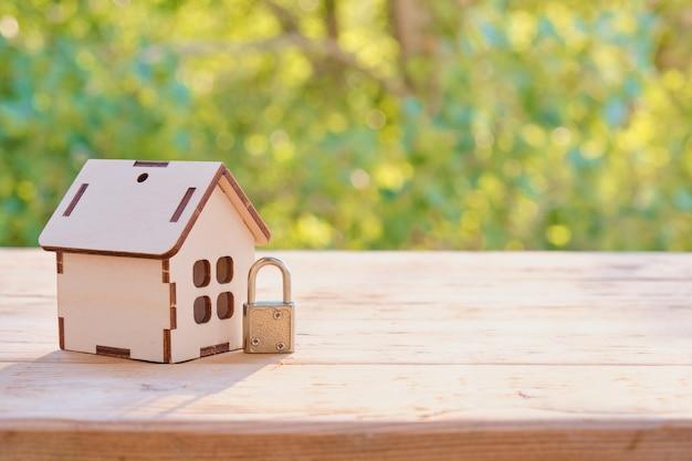 Концепция домашней безопасности: деревянный модельный дом и замок на деревянной поверхности.