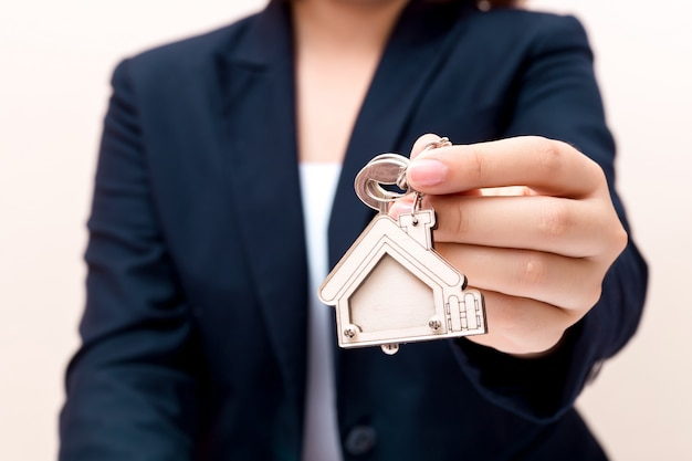 Home seller holding home key. concept for real estate business.