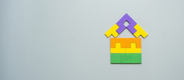 Home shape block with colorful wood puzzle pieces on gray . logical thinking, business logic, solutions, rational, house, real estate and strategy concepts