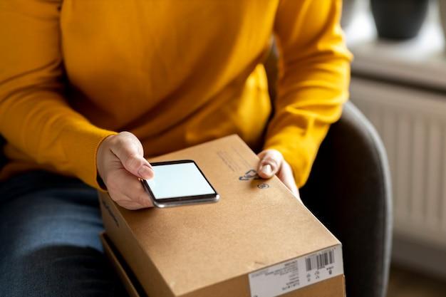 Покупки на дом и концепция доставки на дом. женская рука держит смартфон с пустым экраном дома