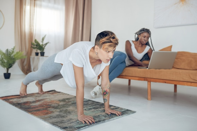 At home. short-haired young girl doing yoga at home while her girlfriend sitting on the sofa