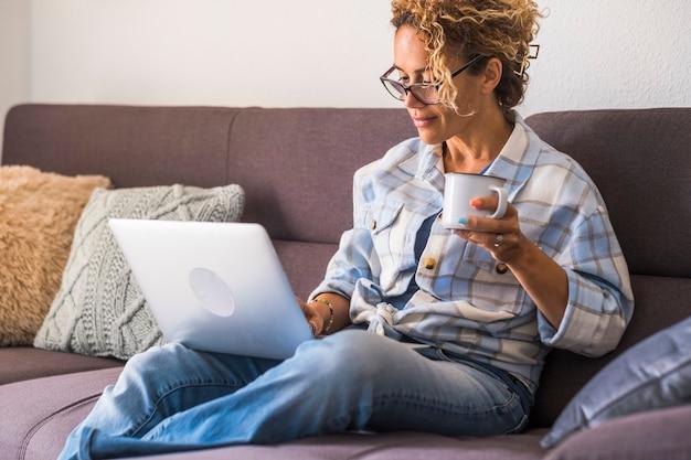 Домашняя одинокая женщина может расслабиться дома, сидя на диване и используя портативный компьютер - покупки или умная работа в сети, женщины - концепция образа жизни в помещении, досуг, технологическая деятельность