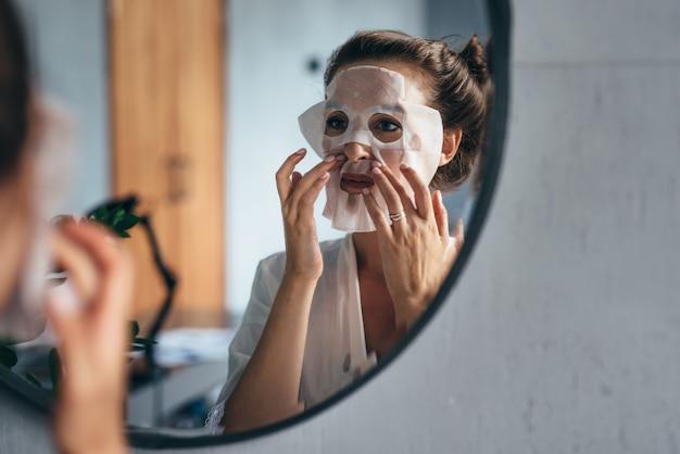 홈 스킨 케어. 한 여자가 얼굴에 시트 마스크를 적용합니다.