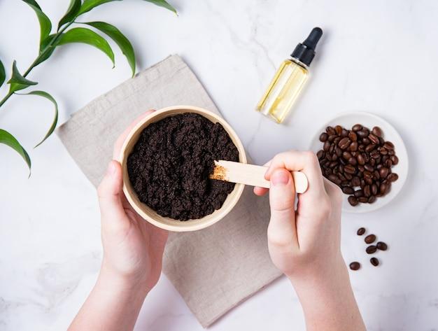 Домашний уход за кожей. молодая женщина смешивает домашнюю кофейную струпу с оливковым маслом на мраморном фоне. вид сверху и плоская планировка