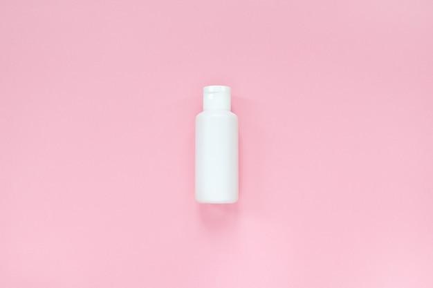 파스텔 핑크의 흰색 병에 담긴 홈 스킨 케어 시스템, 크림, 로션, 토너 또는 토닉