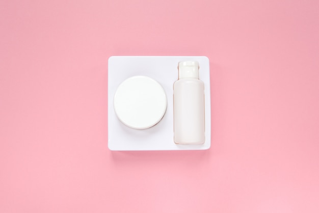 Home skin care system, cream and tonic in white packaging on pastel pink background.