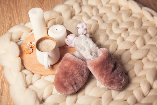Home slippers made of fur, cup of cappuccino and candles on the background of blanket of thick yarn. the atmosphere of homeliness and comfort.