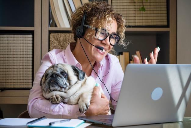 ホームスマートワーキングピープルの仕事ビジネス活動-陽気な若い女性はズームビデオ通話とラップトップコンピューター接続を使用します-オンラインクラスアシスタントと面白い犬の友情を一緒にマーケティングします