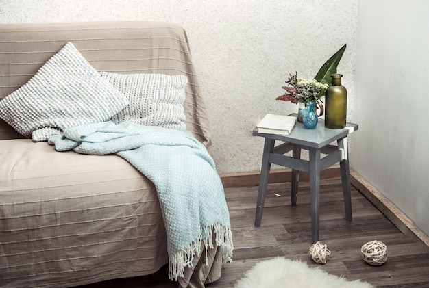 Home sofa with objects of cozy decor in the living room
