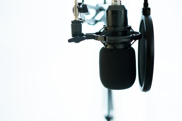 Домашняя студия звукозаписи и оборудование, включая профессиональный конденсаторный микрофон, наушники и портативный компьютер для микширования звука. студия цифровой звукозаписи в домашних условиях.