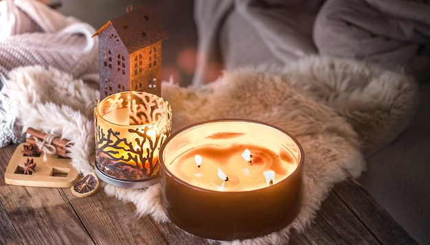 Home still life in the interior with beautiful candles, on the background of a cozy home decor