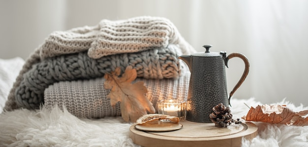 Home still life with knitted sweaters and teapot of tea on blurred background.