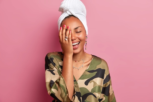 Home style concept. joyful young woman giggles positively, makes face palm, has healthy clean skin after taking shower and cosmetic procedures, dressed in robe, poses against pink wall