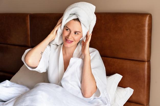 Женщина релаксации в домашнем стиле в халате и полотенце после душа, утро в роскошном отеле