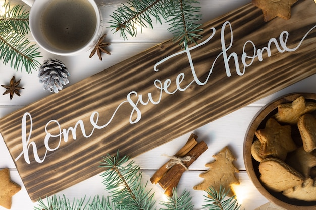 Home sweet home lettering burnt wood sign, gingerbread cookie, christmas tree branches, cup of coffee, cinnamon sticks on white surface. flat lay.