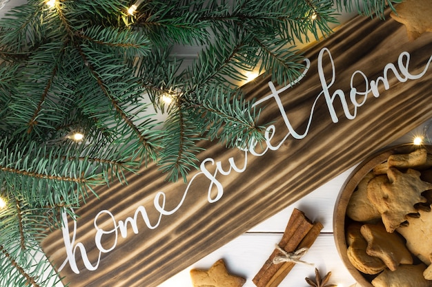Home sweet home lettering burnt wood sign with gingerbread cookie christmas tree branches cinnamon sticks and anise on white surface flat lay