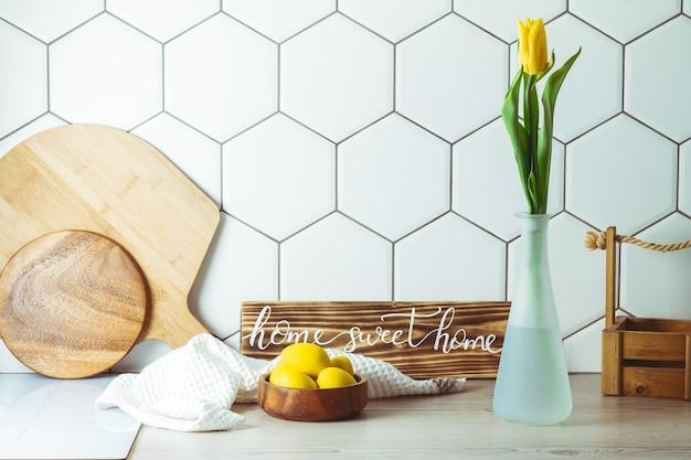 Знак домашнего сладкого дома на кухонной столешнице в деревянной миске с пасхальными яйцами и желтым тюльпаном в вазе