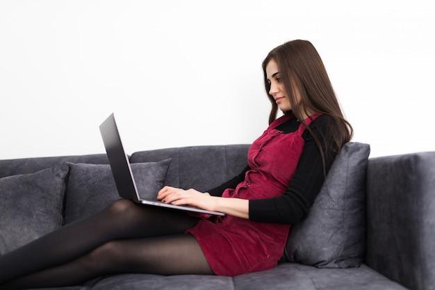 Концепция дома, технологии и интернет. занятая девочка-подросток лежит на диване с ноутбуком дома