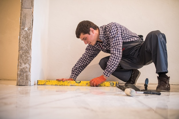 Home tile improvement - handyman with level laying down tile floor