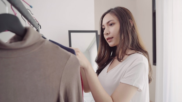 Home wardrobe or clothing shop changing room. asian young woman choosing her fashion outfit clothes