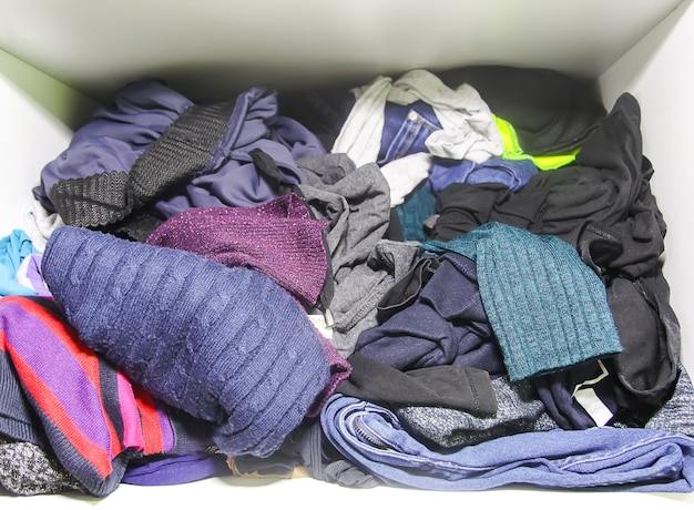 Home wardrobe with different clothes in disorder. small space organization.