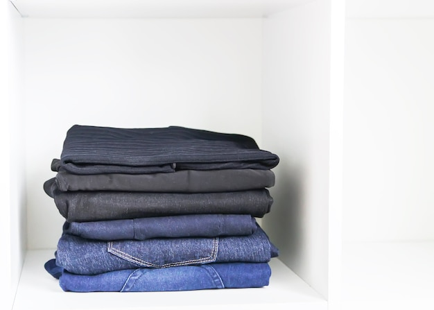 Home wardrobe with different clothes. small space organization. the contrast of order and disorder.