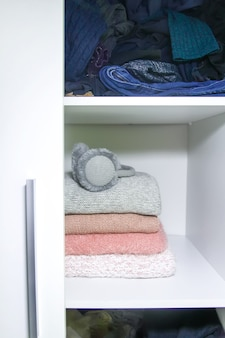 Home wardrobe with different clothes. small space organization. the contrast of order and disorder
