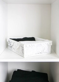 Домашний гардероб с разной одеждой. небольшая организация пространства. контраст порядка и беспорядка. вертикальное хранение.