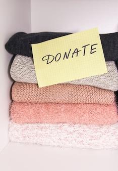 寄付のために分類されたさまざまな服のホームワードローブ。