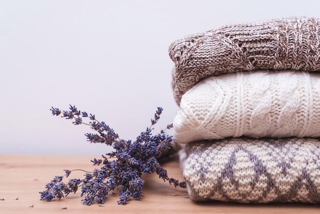 Домашний гардероб с зимней одеждой. шерстяные свитера и сушеная лаванда для защиты от моли. вязаная теплая шерстяная одежда. стек теплой трикотажной одежды с лавандой. осенний, зимний сезон трикотаж.