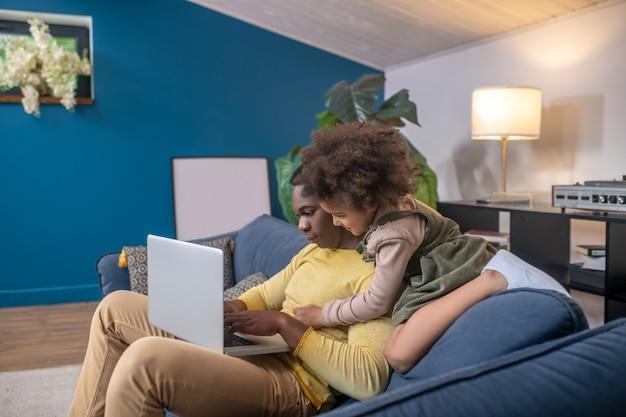 Домашние будни. сосредоточенный афро-американский папа смотрит на ноутбук и скучающая маленькая дочь обнимает плечи, сидя на диване в современной комнате