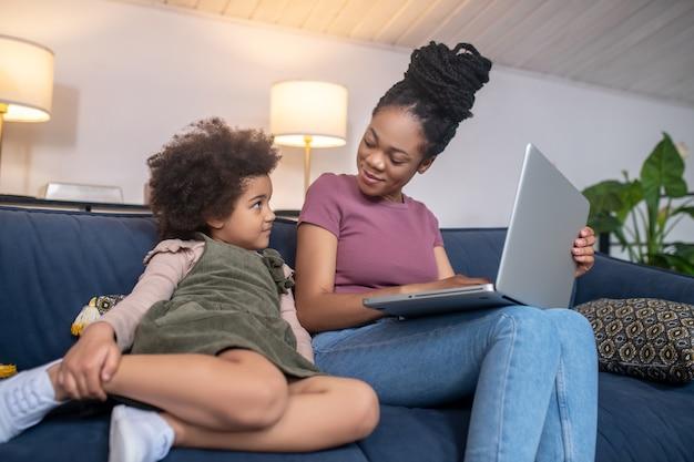 Домашние будни. улыбающаяся африканская мама-амариканка с ноутбуком и скучающая маленькая дочь, сидящая на диване в уютной комнате дома
