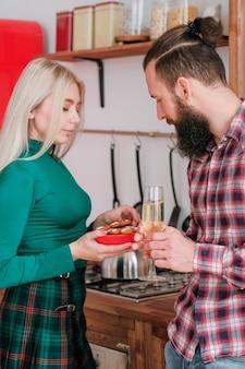 Празднование домашних зимних праздников. пара пьет шампанское на кухне. леди испекла имбирные пряники.