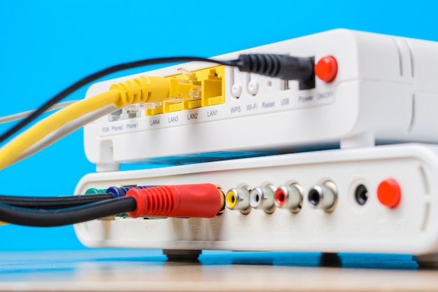Home wireless router with ethernet cables plugged in on blue background, closeup