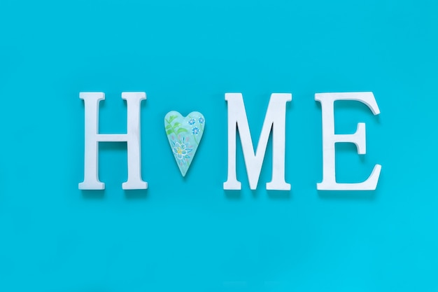 Home, wooden text with heart shape decor on blue background. concept of building houses, choosing your own house, mortgage, buying, selling residential area, rental, insurance, investment real estate.