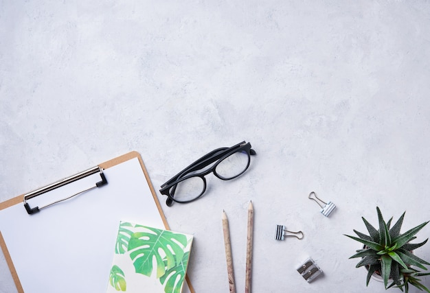 Home work. business flat lay with note, pencil, eye glasses  and cucculent, on white beton background