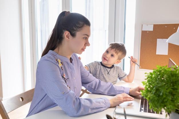 Концепция домашней работы. работа из дома во время пандемии коронавируса covid-19. мать работает на дому, пока ее ребенок играет