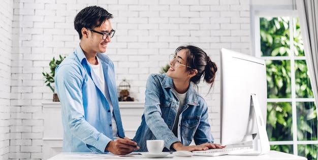 デスクトップコンピューターの作業とビデオ会議のオンラインチャットを使用してリラックスした若いアジアカップル。創造的なビジネスカップルの計画とホームコンセプトからhome.workでブレーンストーミング