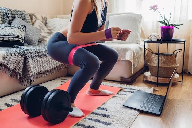 Home workout during coronavirus quarantine. woman training booty glutes. squates