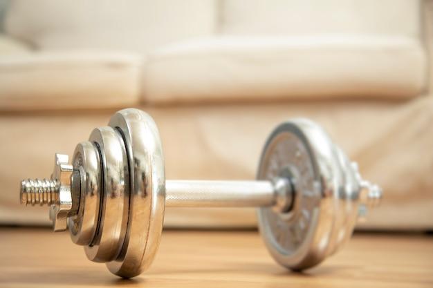 Домашняя тренировка веса тренировки с концепцией гантели и предпосылкой кушетки.