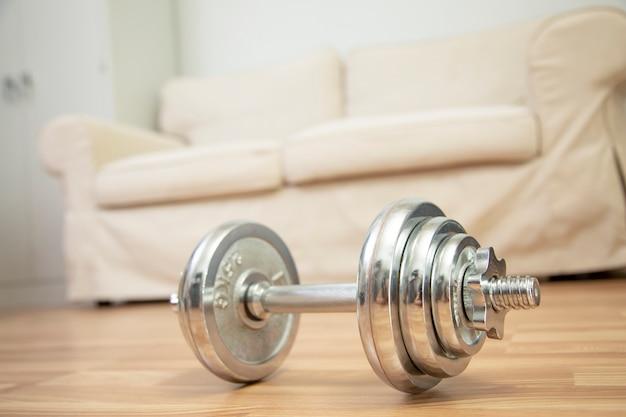 ダンベルの概念とソファの背景を持つホームワークアウトウェイトトレーニング。