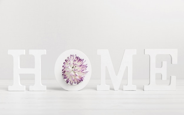 Home written with white letters and beautiful flower