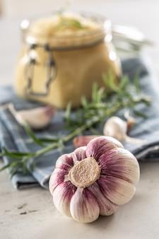 ローズマリーと一緒にキッチンクロスの上に置かれた新鮮なニンニクペーストでいっぱいのガラス瓶の前にある自家製のニンニクの球根。