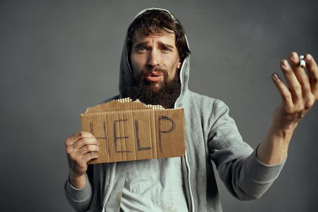 タバコのサインの助けを借りてホームレスのひげを生やした男のトランプ