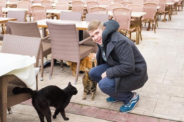 ホームレスの猫、ペット、動物のコンセプト-男は通りの猫を愛撫します。