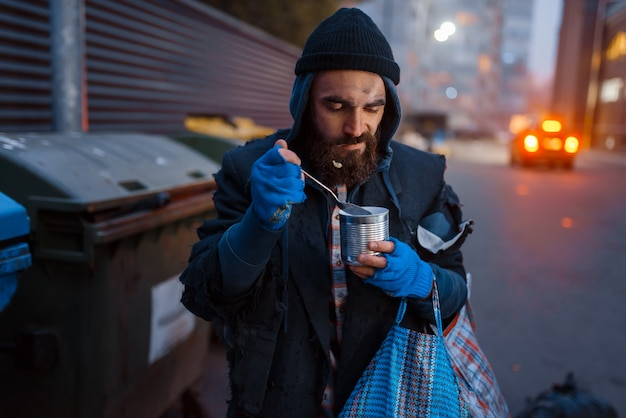 Homeless eating canned food on city street.