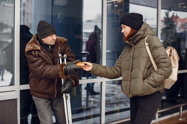 冬の街でホームレス。食べ物を求める男。