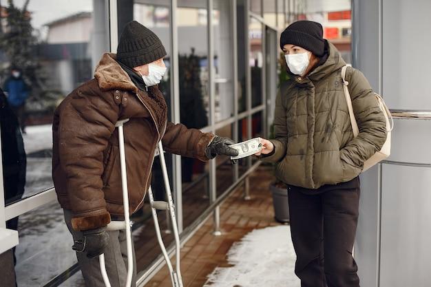겨울 도시의 노숙자. 음식을 요구하는 남자.