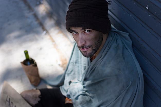Бездомный мужчина и бутылка алкоголя