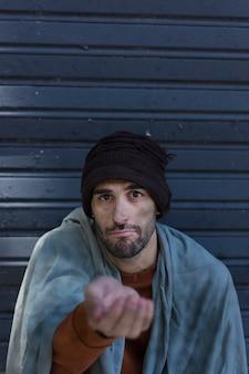 Бездомный мужчина просит денег вид спереди